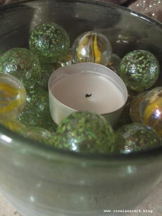 Für die Mitte: ein Glas mit Murmeln und ein Teelicht.